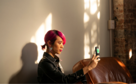 A non-binary femme using their phone.